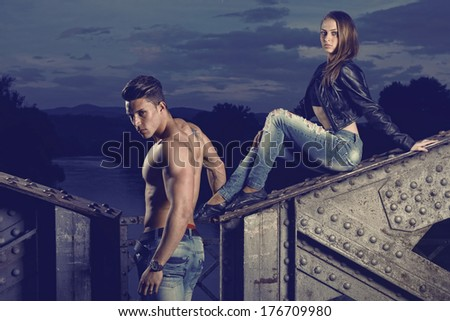 Sexy and fashionable couple wearing jeans, shoot in a grungy location - landscape orientation with copy-space Photo has an intentional film grain) .Fine art.  - stock photo