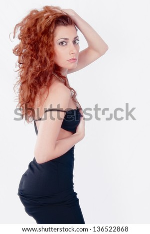 Sexy and sensual redhead in black dress posing for us. Hi key and soft focus.