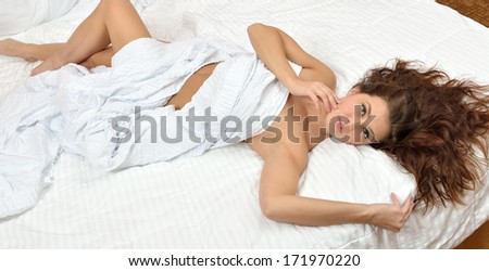Sexy and stunning young brunette woman laying on bed with only a white sheet covering her body