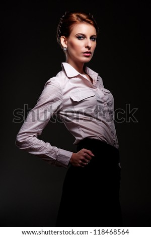sexy and stylish woman in white shirt posing over dark background - stock photo