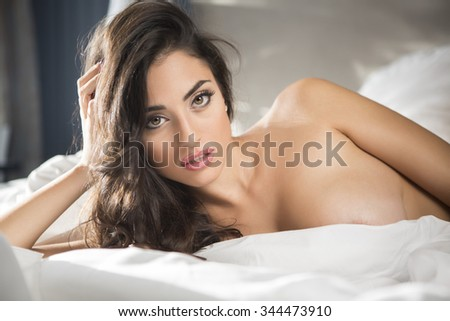 Sexy and voluptuous woman in bed - stock photo