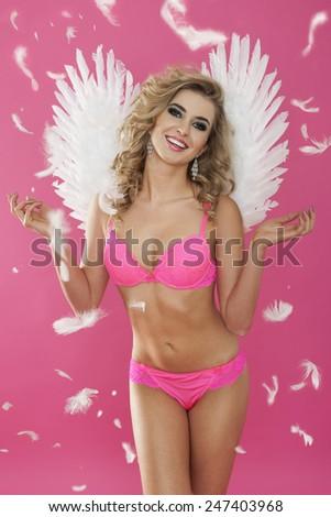 Sexy angel enjoying the falling feathers - stock photo