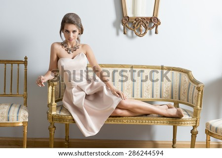 sexy aristocratic girl with pink dress, elegant hair-style and precious necklace lying on vintage sofa in luxury room. Interior fashion portrait