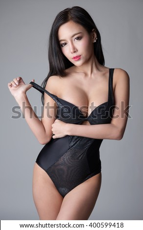 Sexy asian girl wearing black one piece lingerie isolated on white background - stock photo