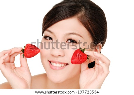 sexy asian woman holding a juicy strawberry near her lips - stock photo