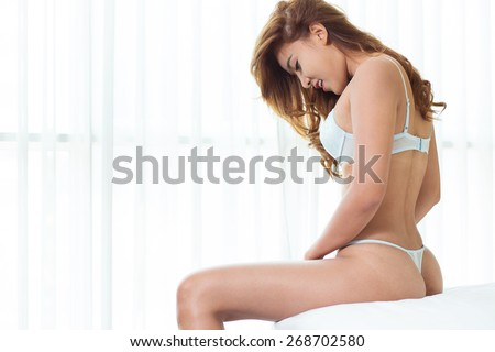 Sexy asian woman in lingerie posing on the bed - stock photo