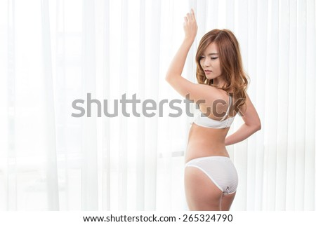 Sexy asian woman in lingerie posing with curtain in the bedroom - stock photo