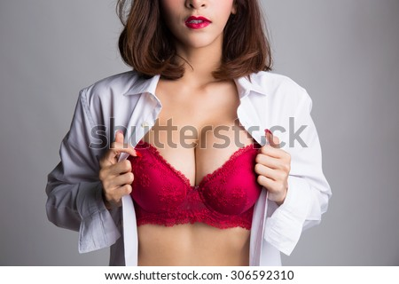 Sexy asian woman showing her sexy breast in red bra or  lingerie with shirt opened by her hand - stock photo