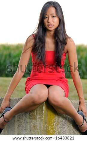 Sexy Asian woman sitting on concrete in front of field in red dress - stock photo