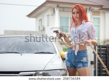 Sexy asian woman washing a car - stock photo