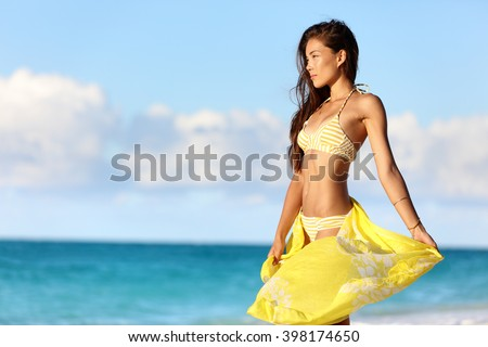 Sexy Asian woman with a slim stomach bikini body relaxing in sunset with yellow pareo cover-up swimwear and beachwear enjoying her weight loss on beach summer vacation in the Caribbean. - stock photo