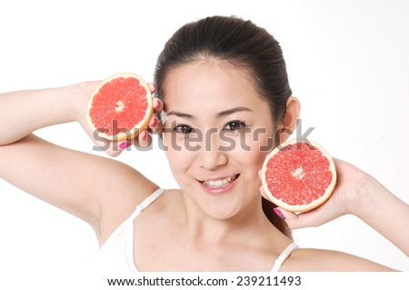 sexy asian young woman holding slice grapefruit in her hands