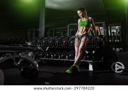 Sexy athlete with a dumbbell in the gym lean on dumbbell row - stock photo