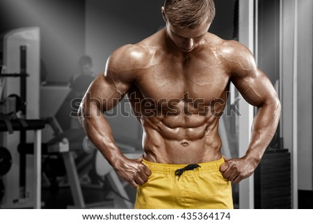 Sexy athletic man showing muscular body and sixpack abs in gym. Strong male nacked torso, working out