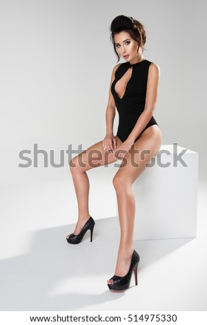 Sexy attractive brunette woman posing in fashionable lingerie in studio