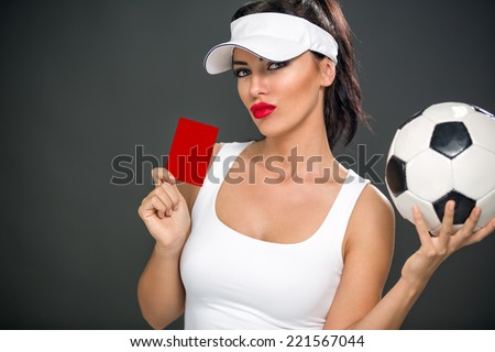 Sexy attractive woman giving red card and holding soccer ball - stock photo