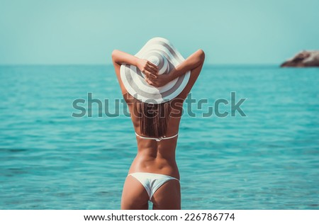 Sexy back beautiful woman at the sea coast - with toning - stock photo