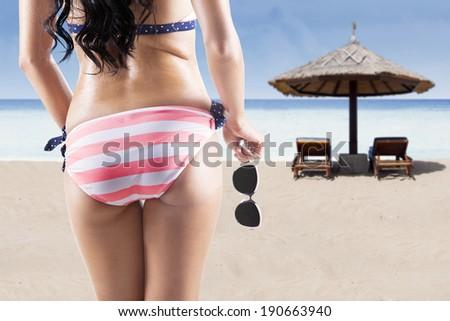 Sexy back of a beautiful woman in bikini on sea background - stock photo