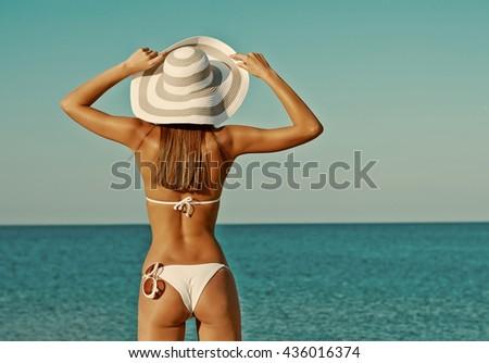 Sexy back of a beautiful woman in bikini on sea background. Sexy buttocks. Retro vintage toned image, film simulation. - stock photo