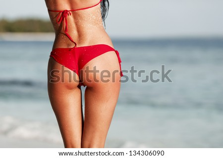 Sexy back of a beautiful woman in red bikini on sea background - stock photo