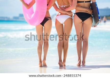 Sexy backs of three beautiful women in bikini on sunny beach. Group of young beautiful girls having fun at beach - stock photo