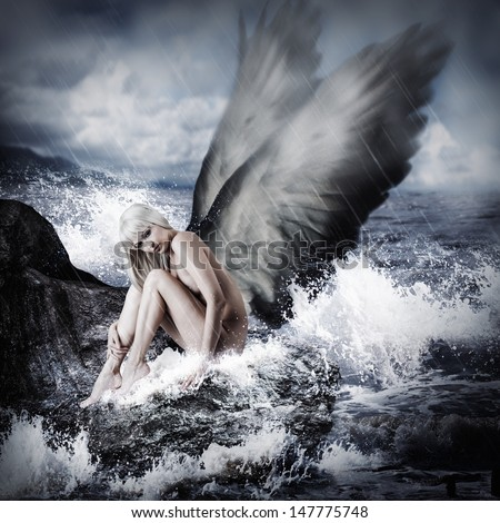 Sexy beautiful blond woman with angel wings sitting on a rock in the sea in storm - stock photo