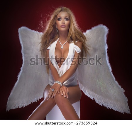 Sexy beautiful blonde angel posing in elegant lingerie. Studio shot. Lady with long healthy hair. - stock photo