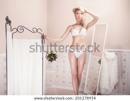 Sexy beautiful blonde woman in white delicate lingerie posing in vintage room.  - stock photo