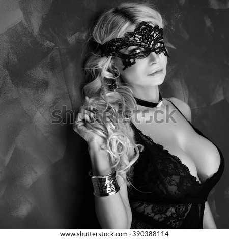Sexy beautiful blonde woman posing in elegant black lingerie and mask, looking at camera. Perfect body.