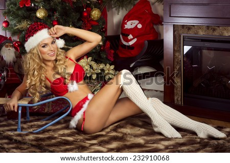Sexy beautiful blonde woman posing in Santa Claus costume at home. Christmas time. - stock photo