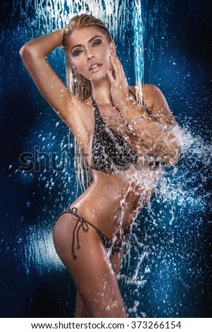 Sexy beautiful blonde woman with perfect fit body posing in swimsuit. Wet body. - stock photo