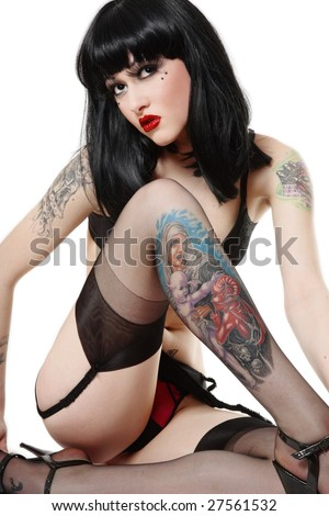 Sexy beautiful brunette with tattoos sitting in white background and looking upwards - stock photo