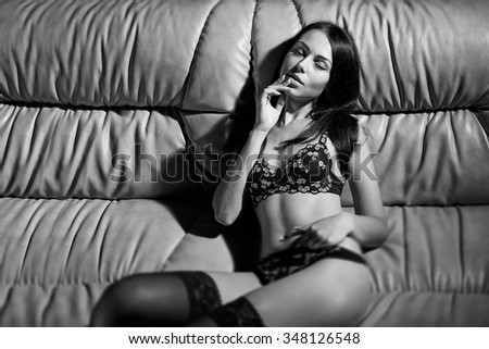 Sexy beautiful brunette woman posing on sofa wearing sensual black lingerie, with closed eyes, black and white image - stock photo