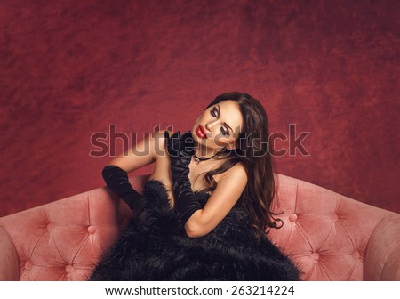 Sexy beautiful brunette woman posing sitting in black vintage gloves and fur on naked body on a luxury pink velvet sofa, dreaming with closed eyes. Velvet dark background with copyspace - stock photo