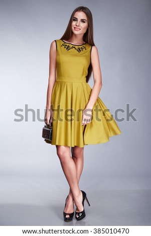 Sexy beautiful brunette woman with long hair wear stylish fashionable branded clothes yellow short dress casual high heel shoes new spring collection accessory lather small bag natural makeup body fit - stock photo