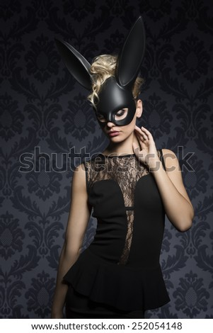 Sexy, beautiful, charming, blonde woamn in black rabbit mask and elegant black dress. - stock photo