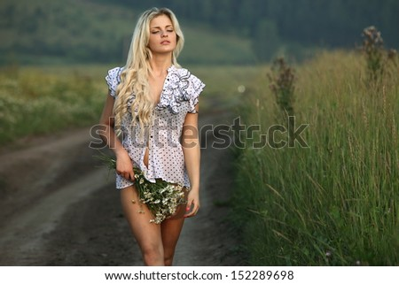 sexy beautiful girl in the road with flowers at sunset - stock photo