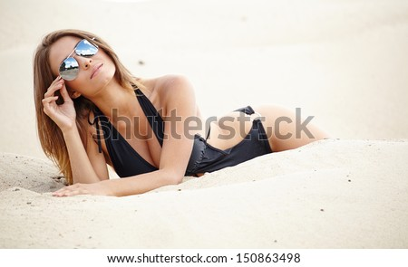 Sexy beautiful girl sunbathing on sandy beach - holiday vacations