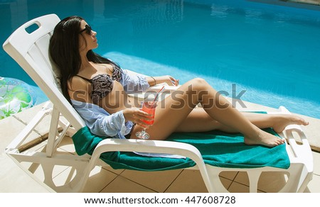sexy beautiful girl with black hair in bikini relaxing beside a swimming pool with cocktail
