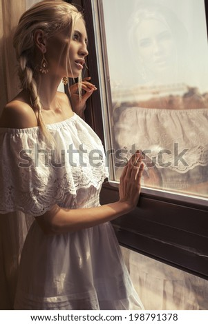 sexy beautiful girl with blond hair dreaming beside a window