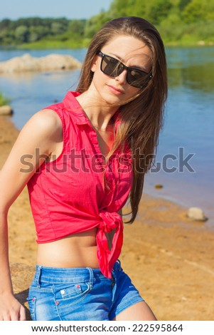 sexy beautiful girl with long dark hair wearing sunglasses sitting in denim shorts on the beach near the water on a Sunny day