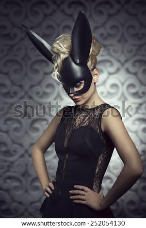 Sexy, beautiful, hot, blonde woman in elegant black dress with black rabbit mask and dark makeup. - stock photo