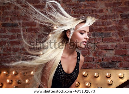 Sexy beautiful makeup woman with long blond streaming, fly away hair posing on yellow star and brick wall background