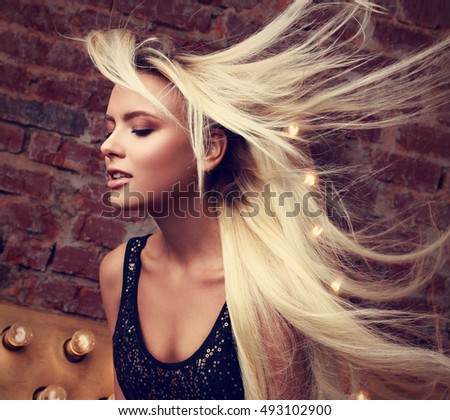 Sexy beautiful makeup woman with long blond streaming, fly away hair posing on yellow star and brick wall background. Toned closeup mystic portrait