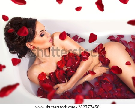 Sexy beautiful naked brunette woman laying in a bath with milk and red romantic falling  rose petals. Luxury spa and skin care - stock photo