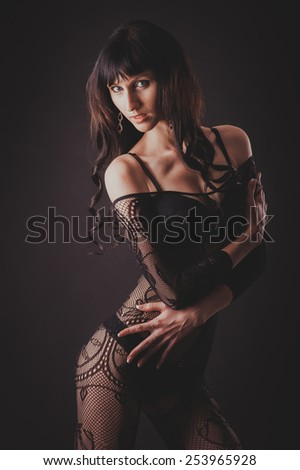 Sexy beautiful naked woman in black erotic lingerie on a black background.