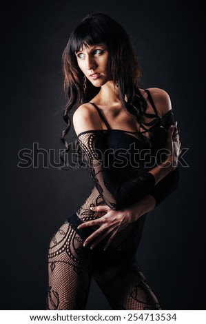 Sexy beautiful naked woman in black erotic lingerie on a black background. - stock photo