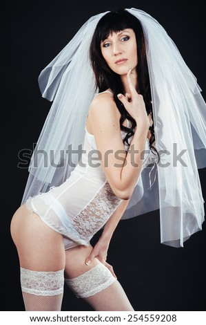 Sexy beautiful nude bride with veil in white erotic lingerie on a black background. - stock photo