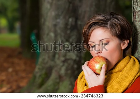 Sexy beautiful serious romantic girl sitting against a tree eating an apple in the park