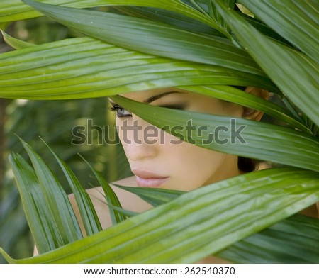 Sexy beautiful woman hiding behind the palm leaves like a panther in the in the tropical forest in India. Portrait of beautiful caucasian stylish young woman with smokey eyes, wildness.  - stock photo